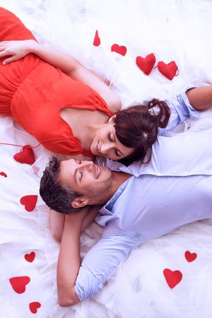愛好家のロマンチックなシーンのバラのベッドに横たわって