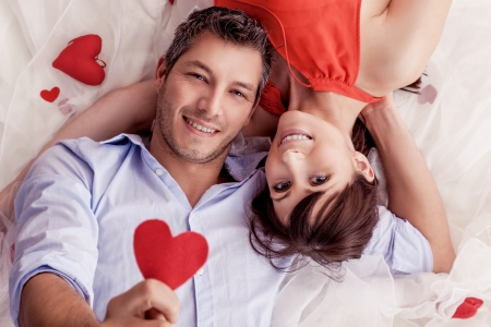 couples hug: smiling rose bed lying lovers Stock Photo