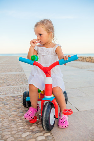 child cycling on summer day on coast photo