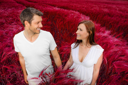happy younger boy and girl walking through red field photo