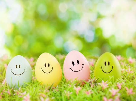 april flowers: smiling easter eggs outdoor in green