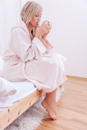 house robe: female relaxing at home sitting on bed beginning day with cup
