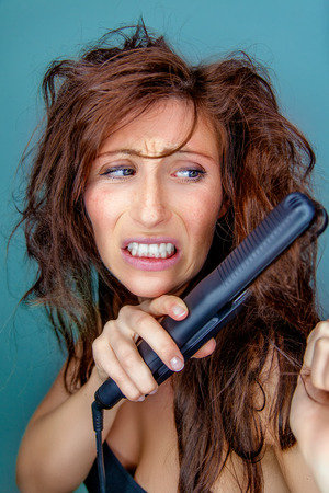 woman preparing for date but getting crazy hair Stock Photo