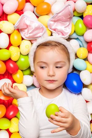 cute little kid child touching painted colorful eggs photo