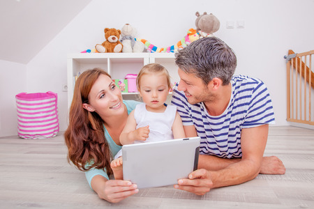 woman with laptop: family playing with tablet showing photos and reading e-book