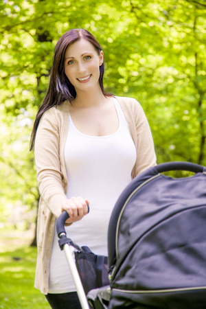 baby carriage: woman driving walking through park  Stock Photo