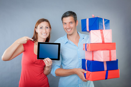 couple with woman advertising with finger on tablet photo