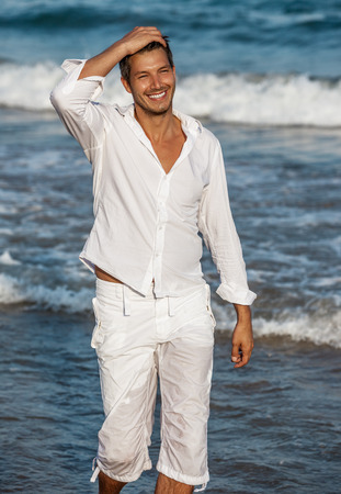 beach hunk: walking down the seaside beach smiling