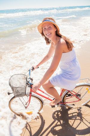 mujer mirando el horizonte: ciclismo mujer feliz en la playa