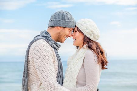 幸せな冬の海岸キスのカップルをリラックス 写真素材