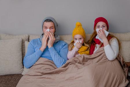 ソファの上のくしゃみのアレルギー病気家族