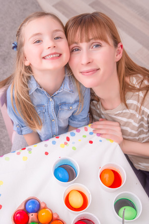 mother with child at room with colorful easter eggs photo