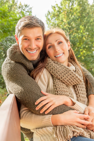 embracing couple in park smiling Banco de Imagens