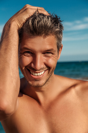 staring at the camera man: attractive man smiling portrait on the beach