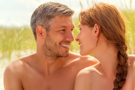 sexy topless women: spa couple smiling eachother on dune
