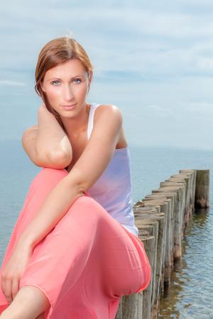 глядя на камеру: Озеро сидит женщина ищет камеру