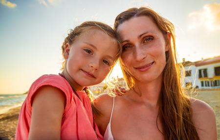 暖かい日にカメラを眺めている母子供 写真素材
