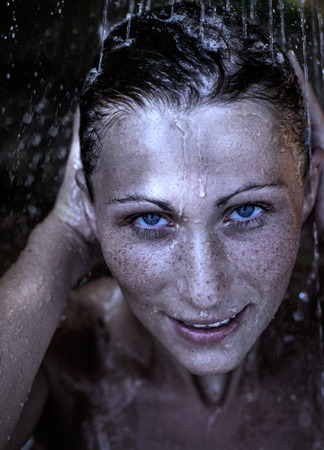 women face stare: female showering outdoors with wet face