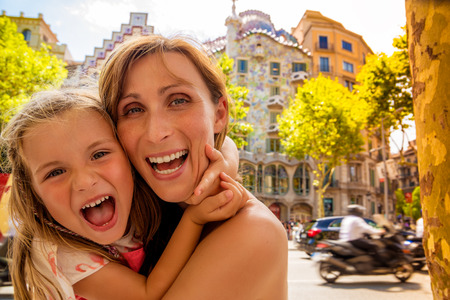 rambla: mother with daughter visiting barcelona rambla with gaudi house background Stock Photo