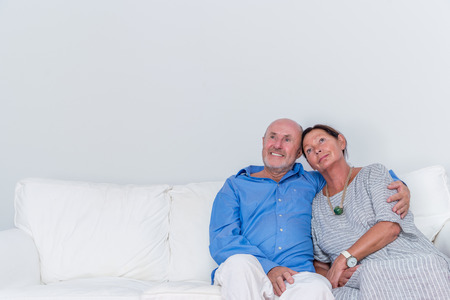 embraced: sitting embraced grandparents thinking Stock Photo