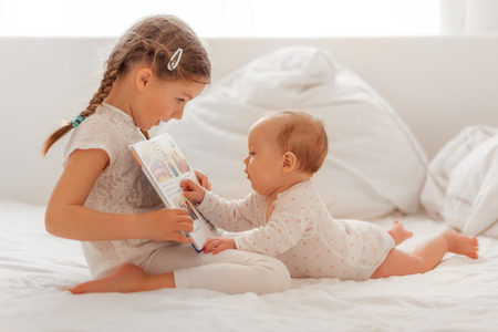 sister explaining and reading baby in bed a book