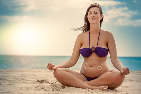 female relaxing pregnant doing yoga curse