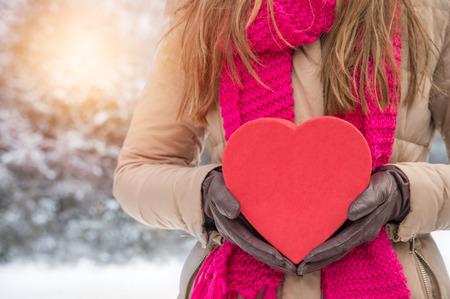 feliz: woman holding a red heard in winter landscape outdoors Stock Photo