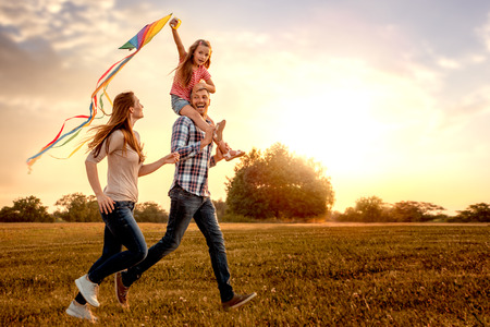 kite flying: family running through field letting kite fly