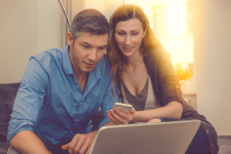 couple booking shopping online with smartphone and notebook Banco de Imagens