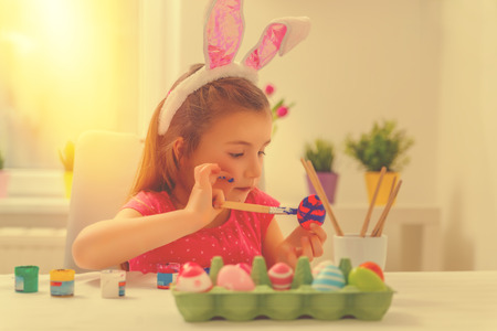 family coloring eggs for easter holiday at home on table