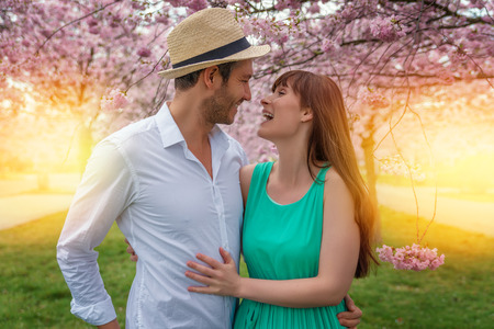 couple outdoors walking with cherry blossom Banco de Imagens