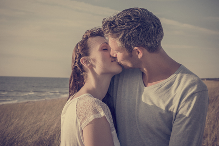 kissing couple on the dunes on the sea