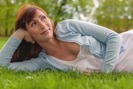 female relaxing on the green ground