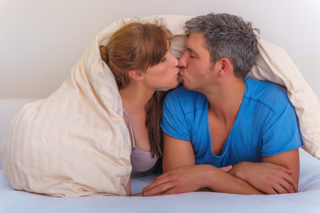 bedroom couple in hotel bed kissing