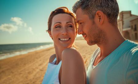 happy mid aged couple on the beach