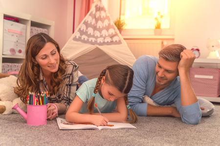 father mother child reading and learning with book at home