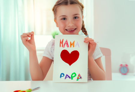 girl surprising parents with greeting card at home Banco de Imagens