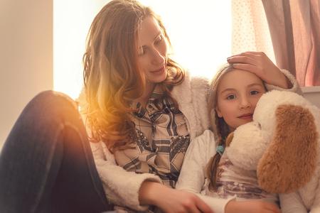 病気中の娘の慰めを与える母