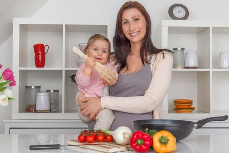 mother cooking with daughter toddler