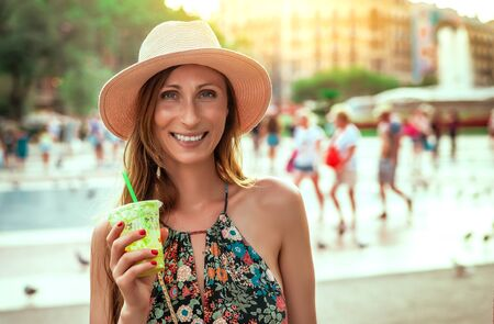 city woman walking with smoothie