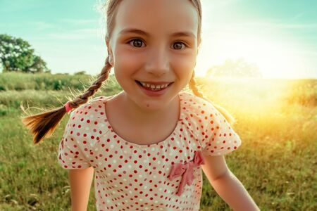 little girl running green meadow field with sunset 版權商用圖片