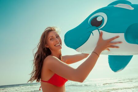 happy female with swimming animal on the beach