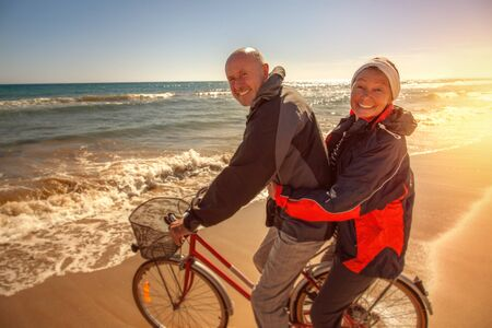 acrive vital senior couple on the coast cycling with bicycle