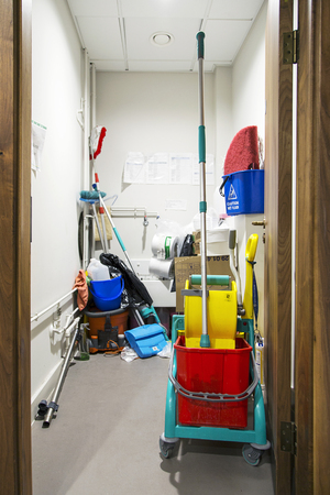 Swansea, UK: June 17, 2017: A storage room full of cleaning equipment including a vaccum cleaner and industrial sized bucket and mop in an office building. Sajtókép