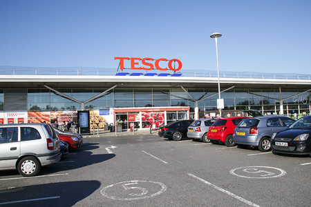 Swansea, UK: June 17, 2017: Main entrance to a Tesco superstore in Swansea. Shoppers are getting into cars or trying to park. Tesco is the UKs largest supermarket chain.