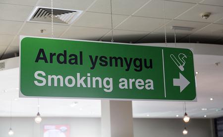 Bilingual Smoking Area Sign at Cardiff Airport Stock fotó