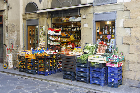Florence, Italy: November 16, 2016: Fruit and vegetables are displayed outside a typical small grocer in Florence, Italy. Every morning the fruit and vegetables are placed outside focustomers Sajtókép