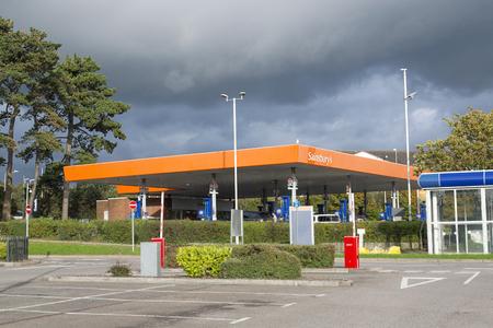 Bridgend, UK: September 25, 2017: Customers use the self service dispensers to refuel at a Sainsbury's petrol station Redakční