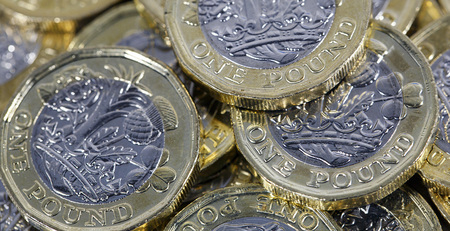Close up of British one pound coins in a panoramic format