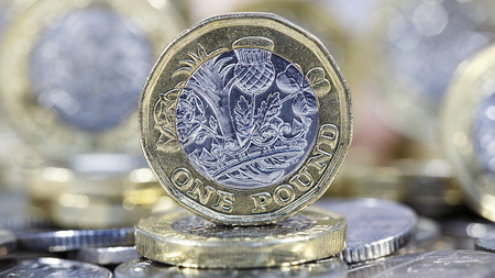 British Sterling. One pound coin standing on other coins with selective focus in a panoramic format Stock fotó